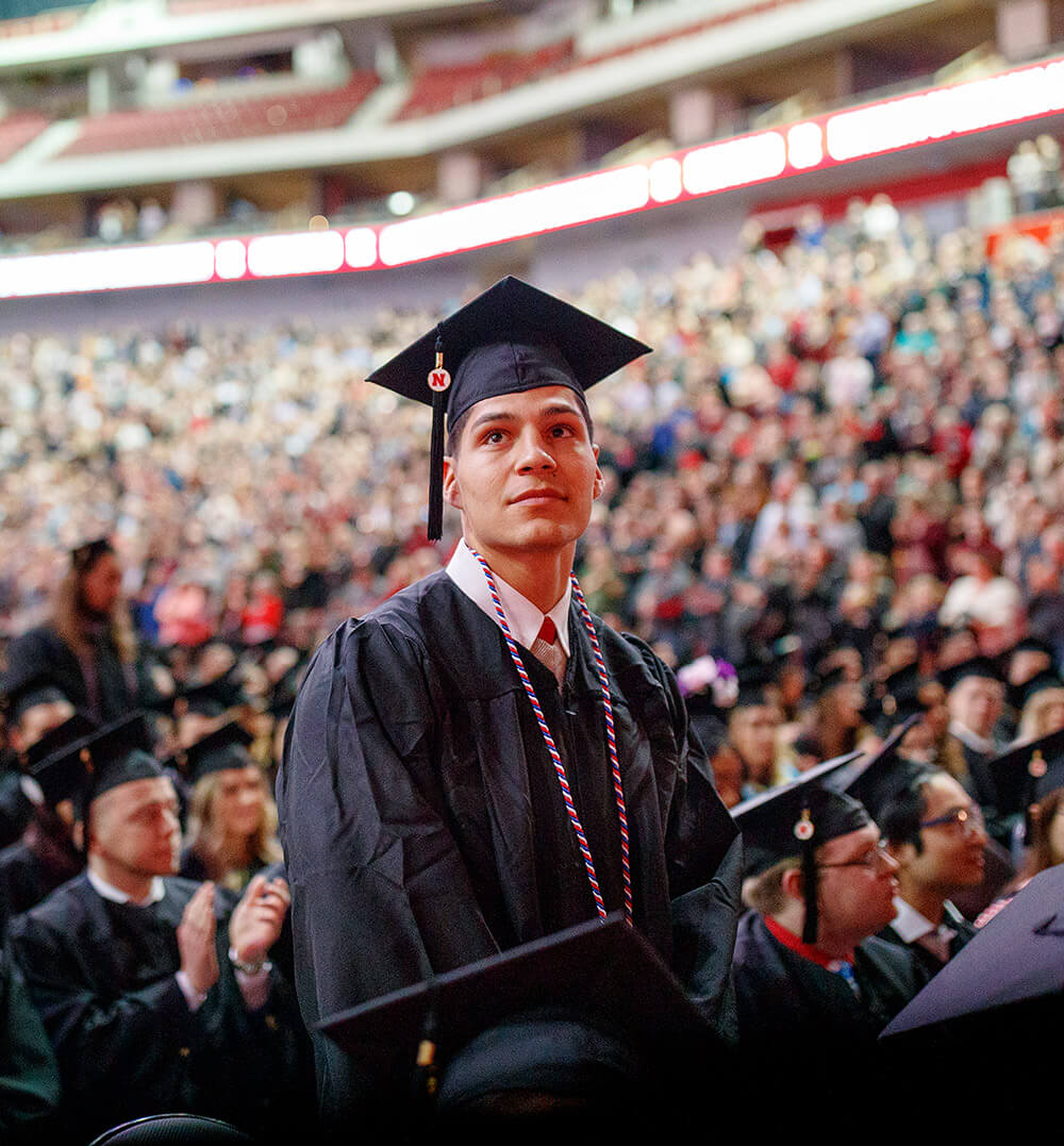 Student standing at undergraduate commencement