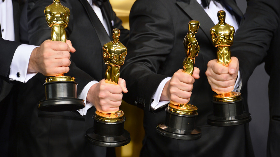 Image of actors holding Academy Award trophies; links to news story Dixon predicts this year's Oscar winners