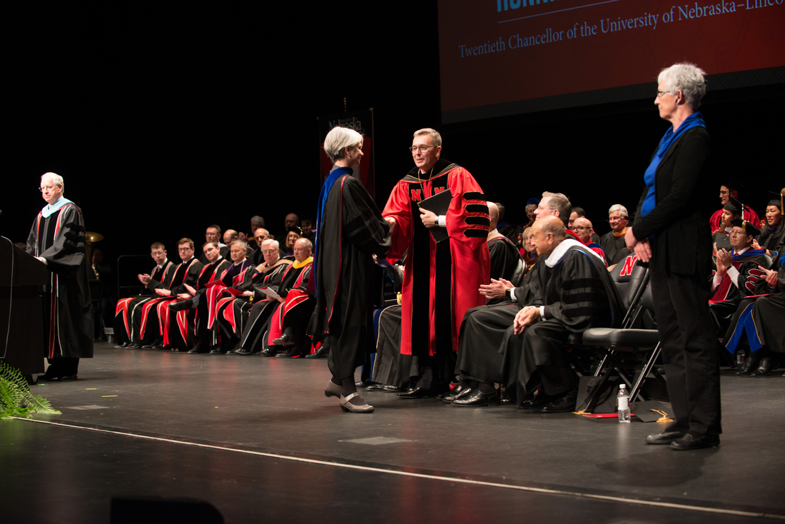 Chancellor Ronnie Green shakes hands with Professor Joy Castro on stage at the installation ceremony