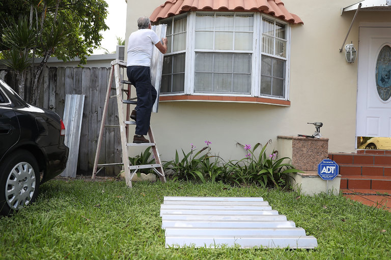 "A man attaching storm shutters on to a house in Miami; links to news story Crucet in the NYT: ""Miami Always Thinks the Storm Will Turn"""