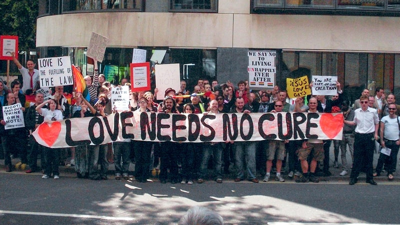 LGBTQ+ protesters hold a banner that says 'Love needs no cure'; links to news story White's novel HOW TO SURVIVE A SUMMER featured in Rolling Stone