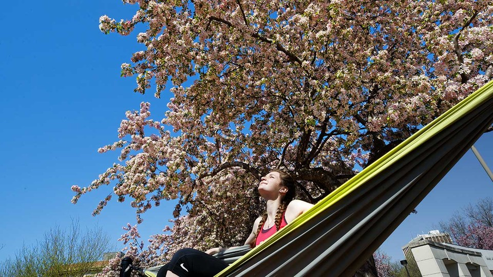 Kelsey Ewert of Ogallala enjoys the sunshine as she sits in a hammock outside the Nebraska Union