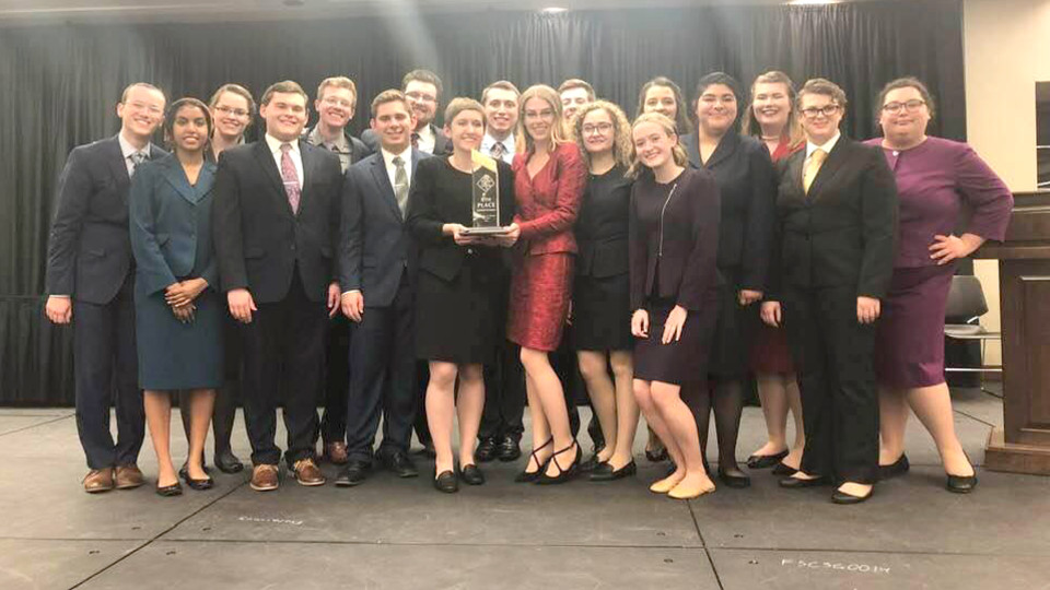 UNL competitors and Becca Human holding her trophy; links to news story