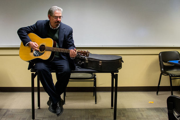 Steve Buhler draws upon his musical talent - playing guitar - to enrich his classes