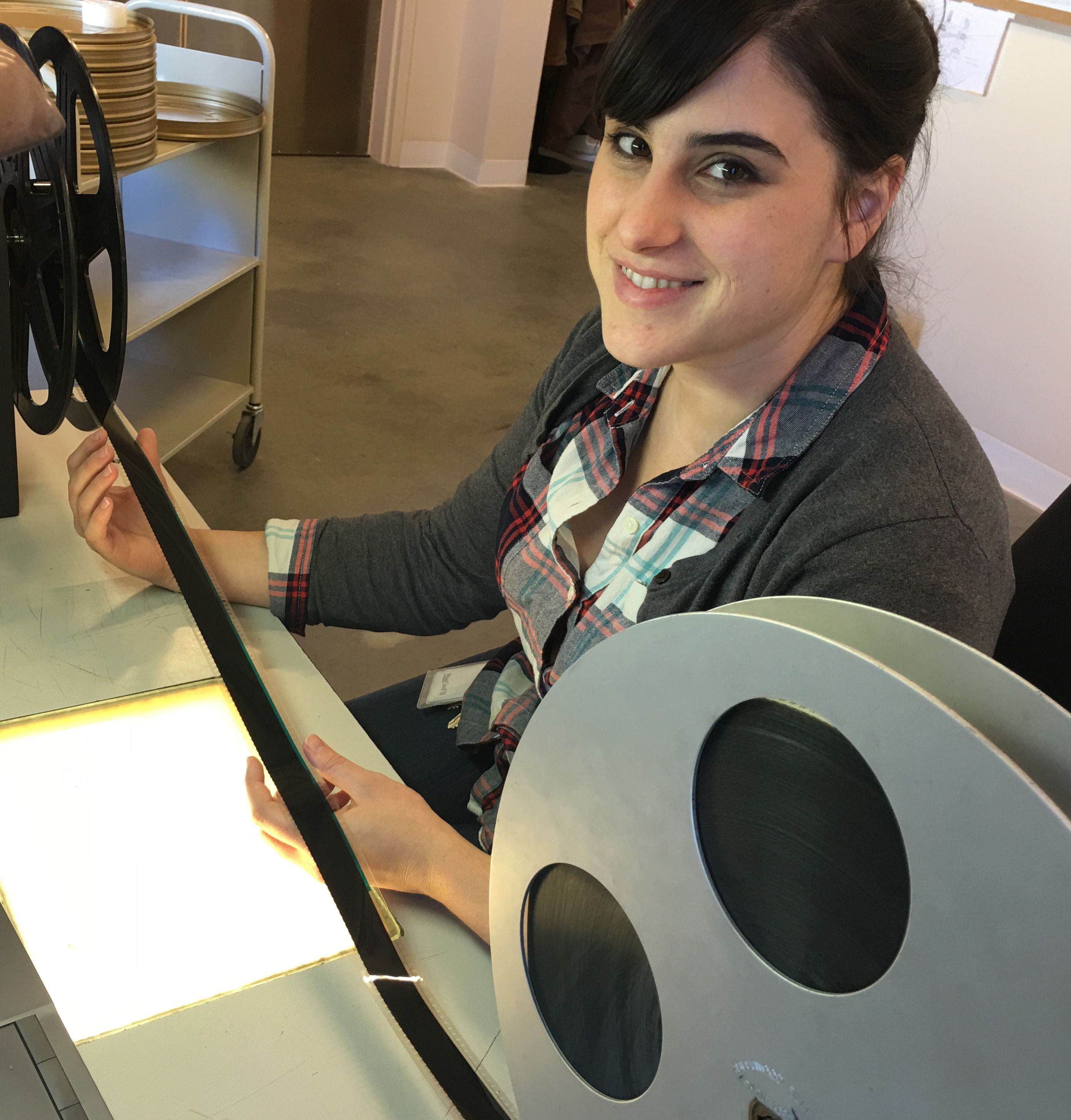 Staci Hogsett examines film reels over a lighted table at the UCLA Film and Television Archive