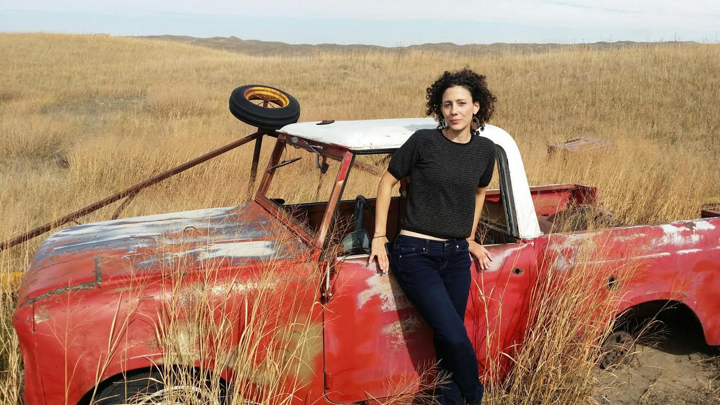 Maria Nazos poses on the Nebraska prairie with a broken down pickup truck