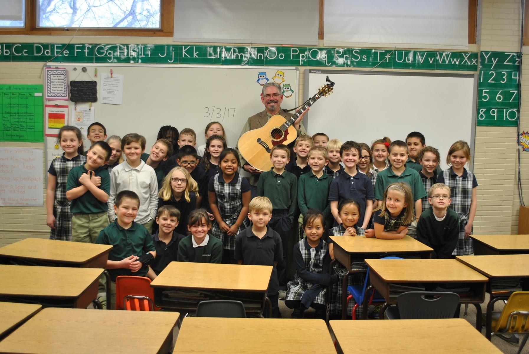 Steve Buhler and his guitar with students at Cathedral of the Risen Christ School