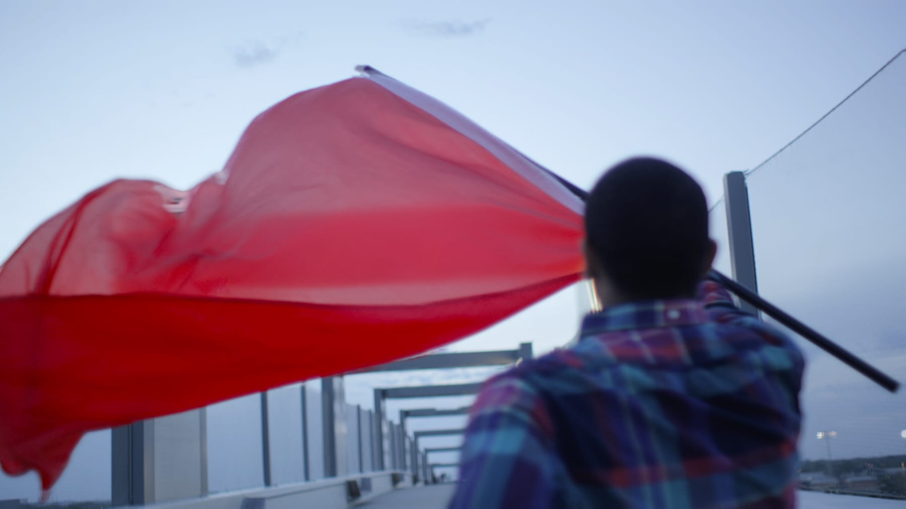 A student carries a large red flag near Pinnacle Bank Arena
