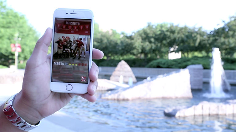 A hand holds a smartphone in front of Broyhill Fountain at the Nebraska Union. A Snapchat story about New Student Enrollment plays on the phone's screen.