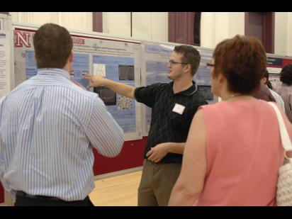 a student presenting his research poster