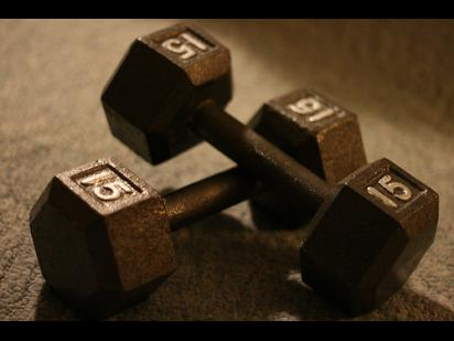 two 15-pound dumbbells on a dark background