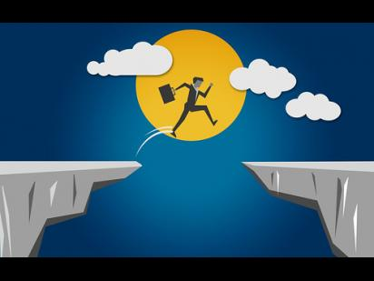 Person jumping through mountain cliffs to success