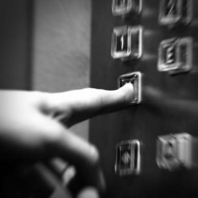 close-up of finger pressing elevator button