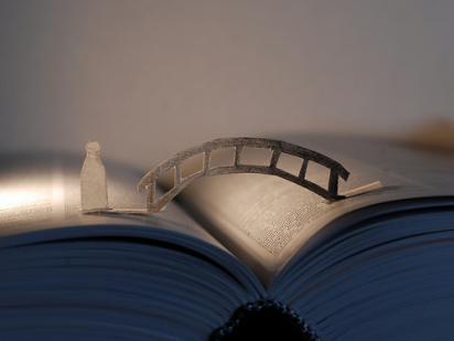 Paper bridge over a book