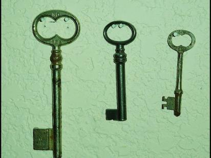 three keys, hanging next to each other on a green background