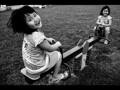 Twins play on a seesaw
