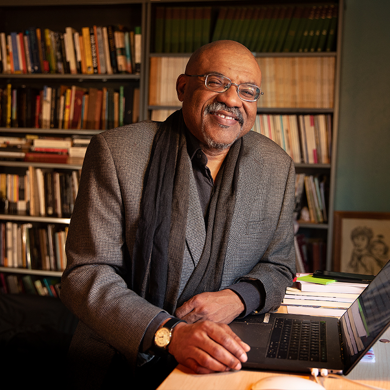 Kwame Dawes stands at his desk with books and past publications of Prairie Schooner behind him