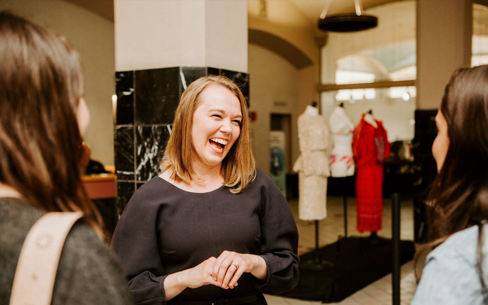 Jennifer Johnson Jorgensen laughs with students in front of dress forms