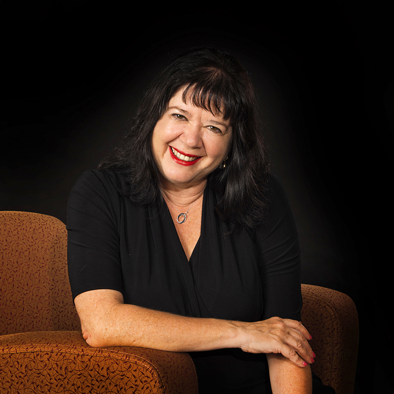 Susan Levine Ourada portait in chair with black background