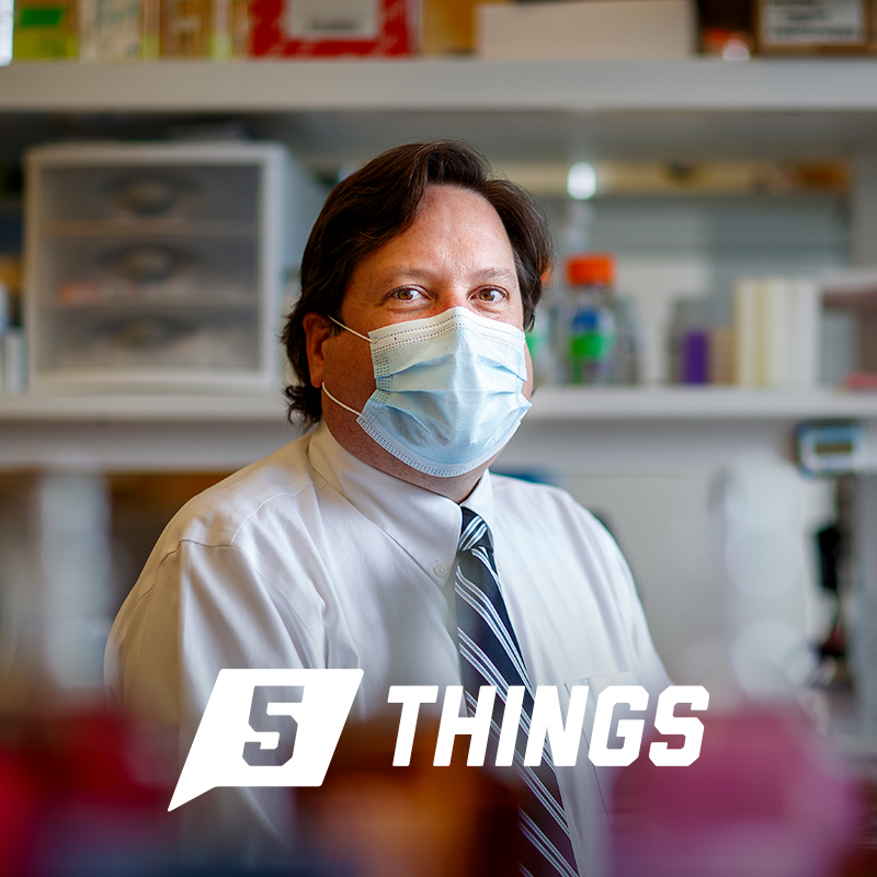 Eric Weaver sits in his lab wearing a mask