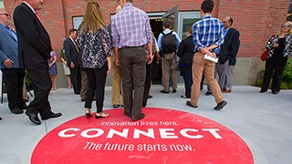 A group of people enter Nebraska Innovation Campus for a tour of the facilities. A large circle decal on the floor reads, 'Innovation lives here. Connect. The future starts now.'