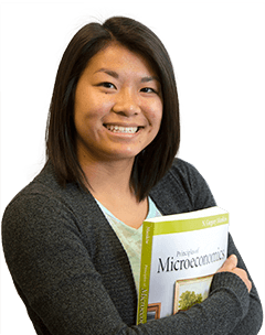 A student holding a microeconomics text book.