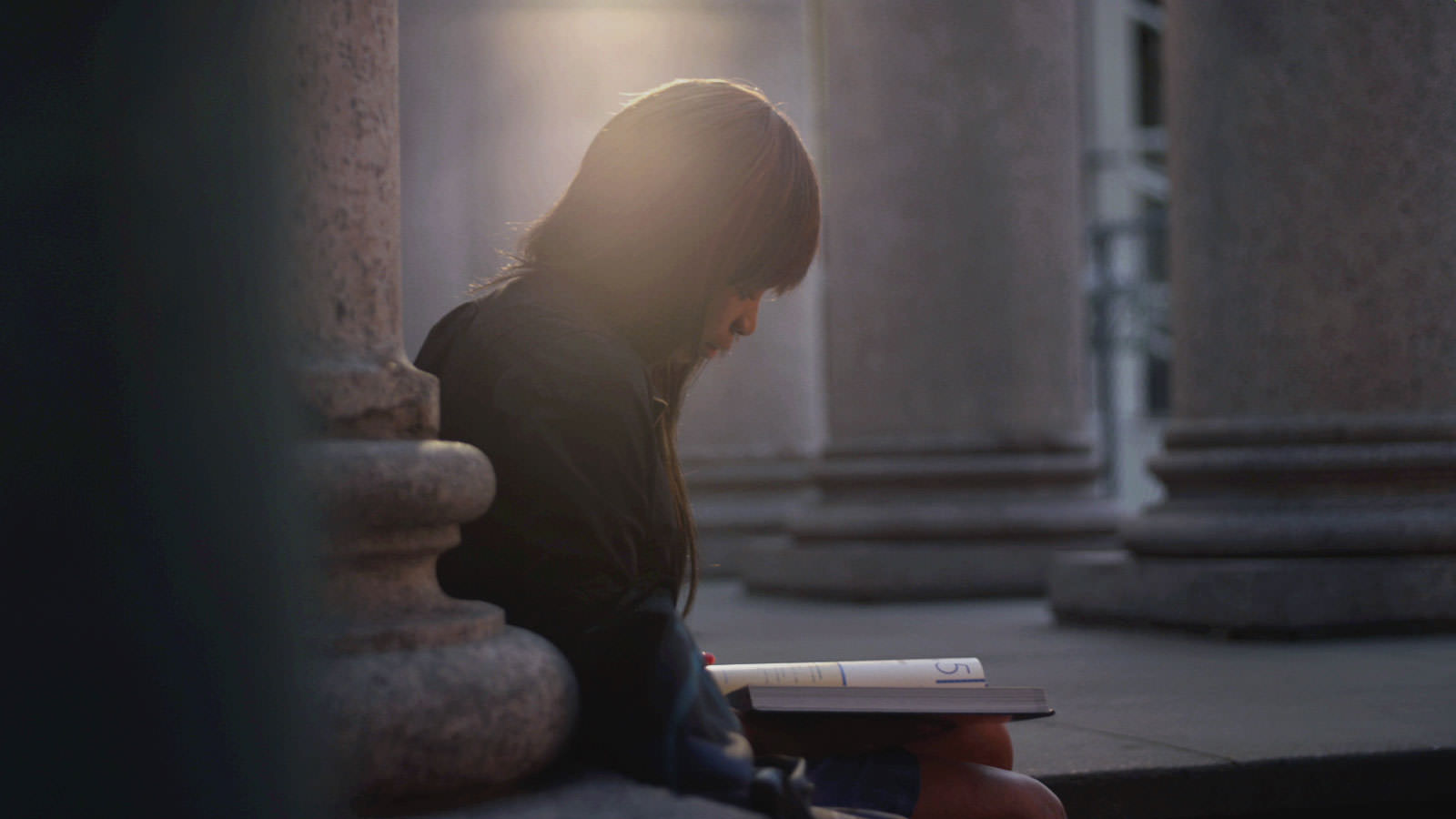 A student sits and reads at the entrance of a building on campus.