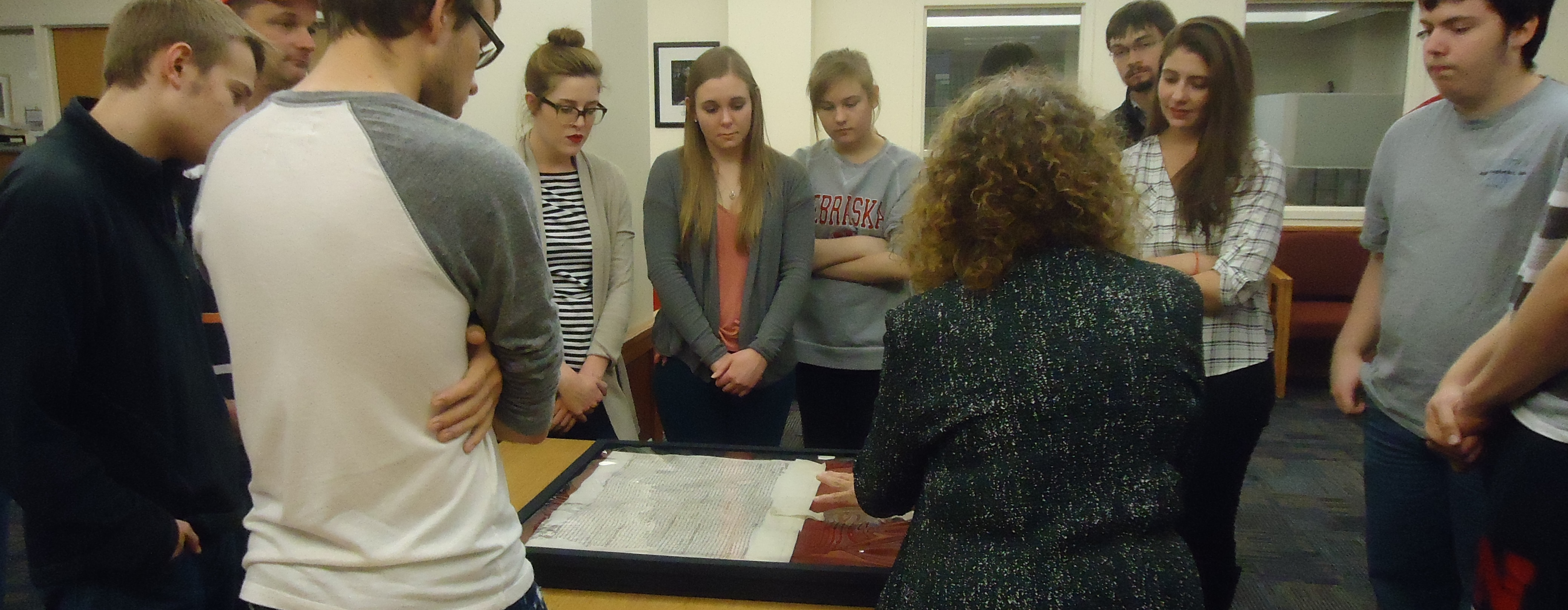 HIST 231 students listen to Dr. Levin describe a land deed with Queen Elizabeth I's pre-1575 seal