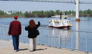 Writers walking along Missouri River, small boat