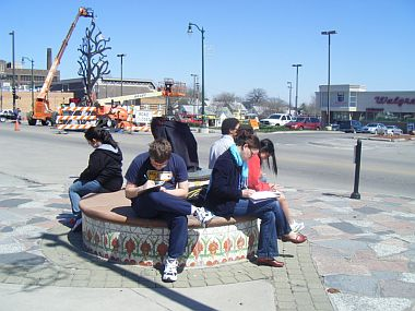 Students writing in Omaha outdoor plaza