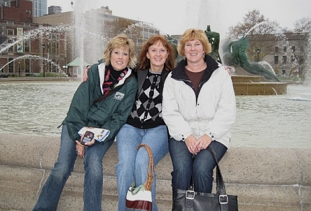 Three women seated by a Fountain