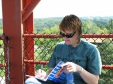 Woman seated on lookout tower, writing