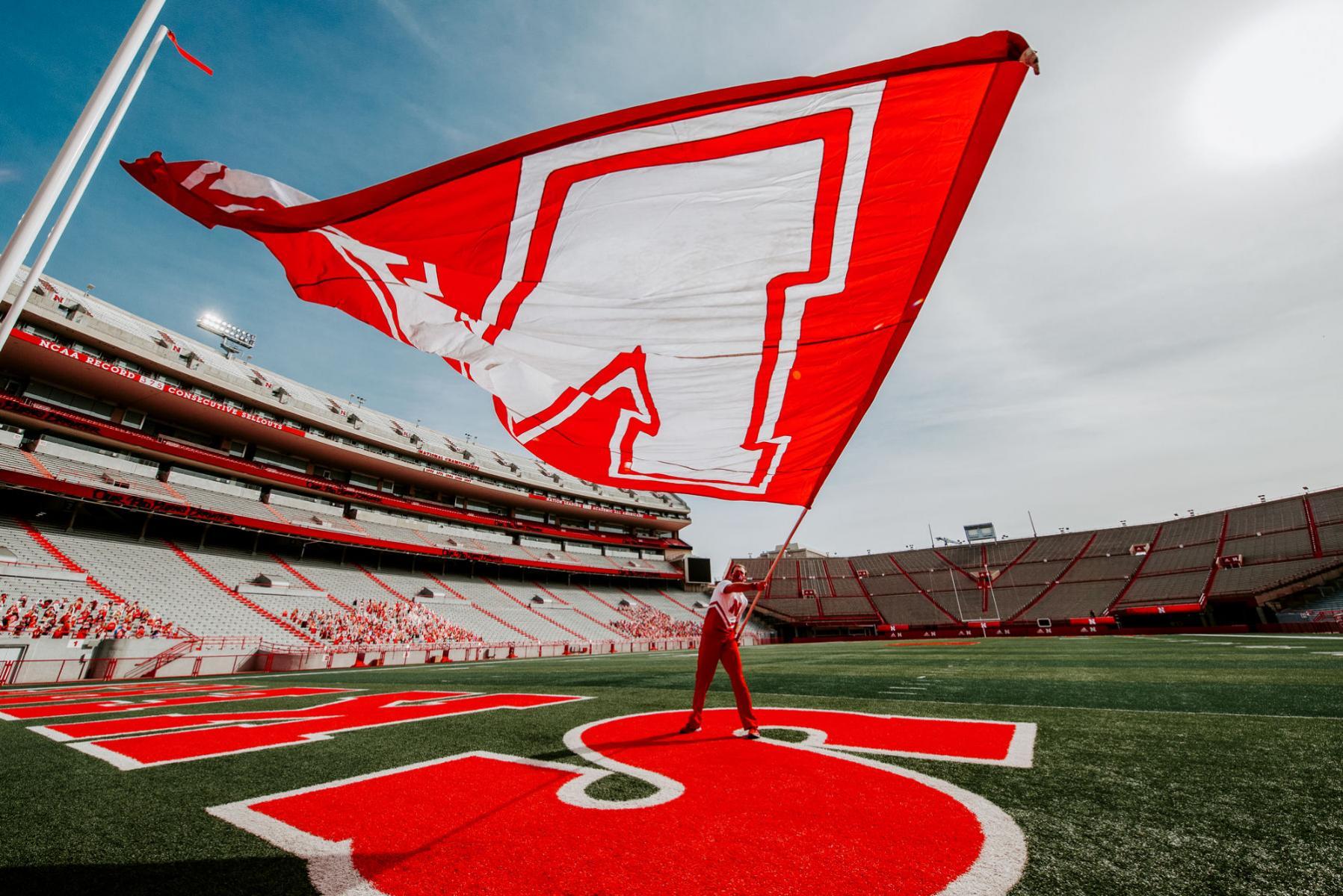 Student waving Nebraska flag while standing on field at Memorial Stadium
