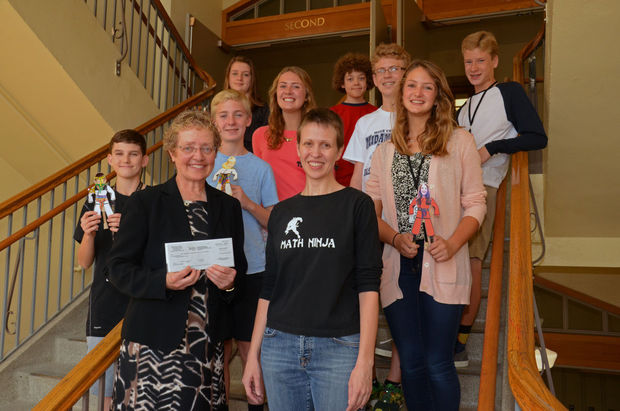 Photo Credit: Jocelyn Bosley presents a check for $2,500 to principal, Susette Taylor, and students.