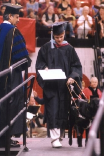 Graduate receiving his diploma while being guided across the stage by his seeing eye dog