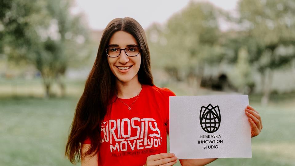 Student holding sign for Innovation Studio