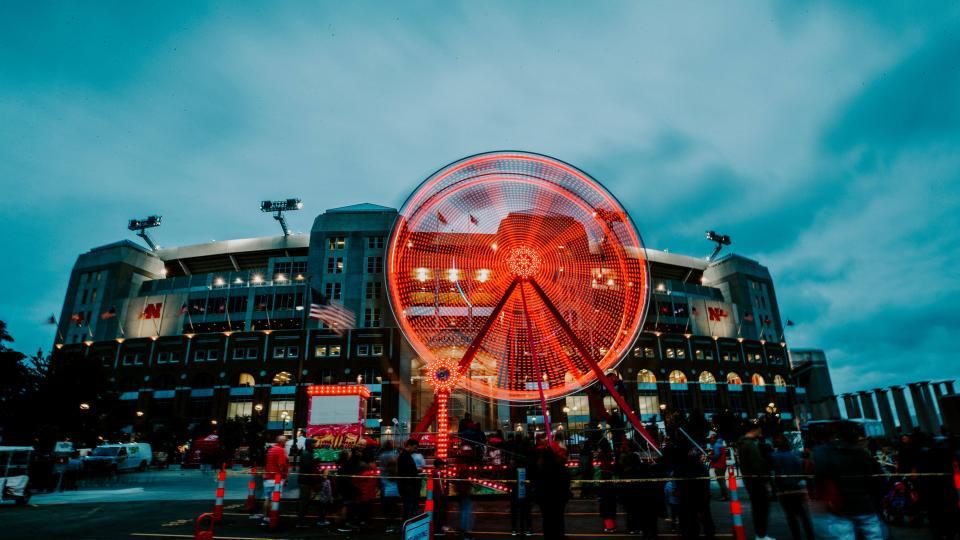 Ferris wheel lit up at dusk in front of Memorial Stadium